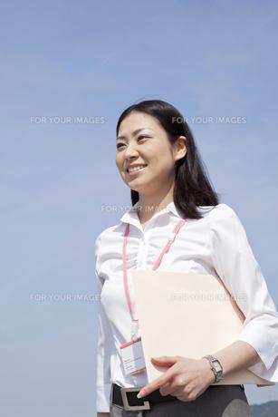 書類を抱える笑顔のビジネスウーマンの写真素材 [FYI00119570]