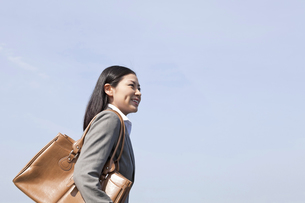 青空の下を歩く笑顔のビジネスウーマンの素材 [FYI00119573]