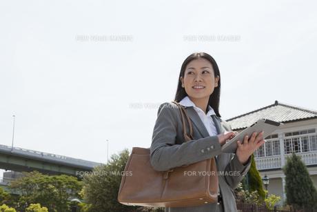 屋外でiPadを操作するビジネスウーマンの素材 [FYI00119575]