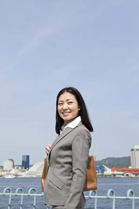 青空の下を笑顔で歩くビジネスウーマンの素材 [FYI00119585]