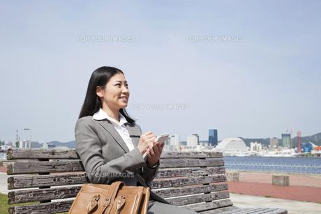 ベンチに座りメモをとるビジネスウーマンの素材 [FYI00119588]