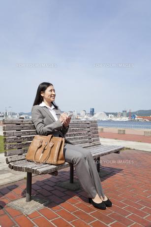 ベンチに座りメモをとる若いビジネスウーマンの素材 [FYI00119592]