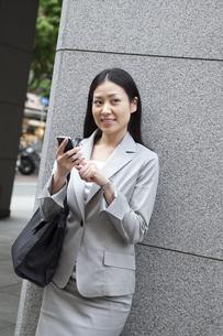 オフィス街でスマートフォンを操作するビジネスウーマンの素材 [FYI00119595]