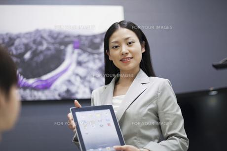 iPadで説明をするビジネスウーマンの素材 [FYI00119601]