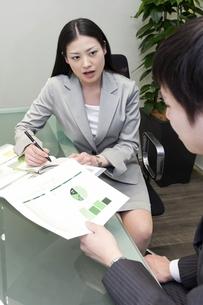 資料を手にミーティングをするビジネスマンとビジネスウーマンの素材 [FYI00119605]