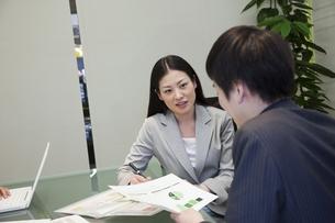 資料を手に話し合うビジネスマンとビジネスウーマンの素材 [FYI00119609]
