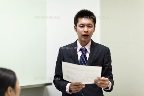 資料を手にプレゼンテーションを行うビジネスマンの素材 [FYI00119614]