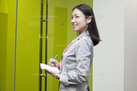 笑顔でメモ帳を手にするビジネスウーマンの写真素材 [FYI00119622]