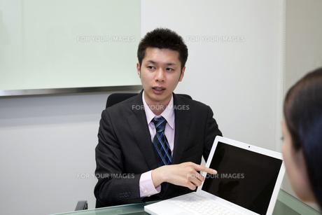 真剣な表情で画面を指さすビジネスマンの素材 [FYI00119638]