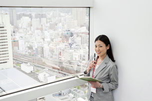 窓際に笑顔で立つビジネスウーマンの写真素材 [FYI00119645]