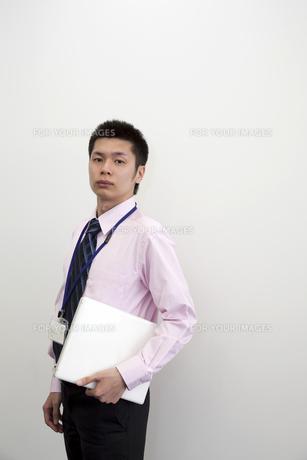 ノートパソコンを抱えるビジネスマンの写真素材 [FYI00119649]