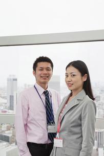窓辺に立つビジネスマンとビジネスウーマンの写真素材 [FYI00119651]