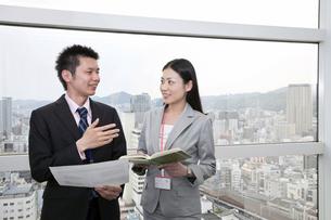 窓辺で会話をするビジネスマンとビジネスウーマンの写真素材 [FYI00119654]