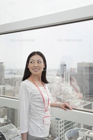 窓辺で振り向くビジネスウーマンの写真素材 [FYI00119657]