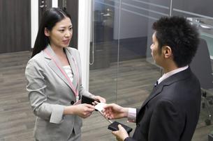名刺を手渡すビジネスウーマンの写真素材 [FYI00119660]