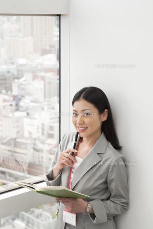 窓辺に笑顔で立つビジネスウーマンの写真素材 [FYI00119671]