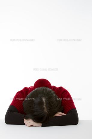 机に顔をうずめる若い女性の素材 [FYI00119904]