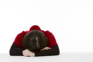 机に顔をうずめる若い女性の写真素材 [FYI00119914]