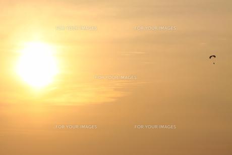 夕暮れの太陽とパラグライダーの写真素材 [FYI00122026]