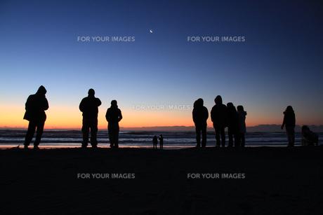 海岸で日の出を待つ群集と朝焼けの月の写真素材 [FYI00122035]