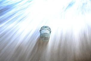 波打ち際で波にさらわれる鳥かごの写真素材 [FYI00122055]