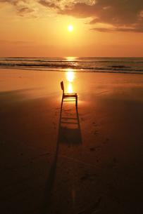朝焼けの浜辺に置き去りの1脚の椅子の写真素材 [FYI00122069]