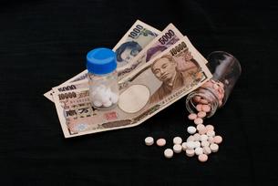 錠剤と紙幣 / 医療費などのイメージの写真素材 [FYI00127871]