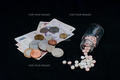 錠剤と外国紙幣、硬貨 / 医療費などのイメージの写真素材 [FYI00127876]