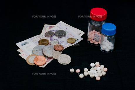 錠剤と外国紙幣と硬貨 / 医療費などのイメージの写真素材 [FYI00127895]