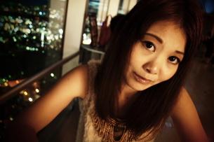 夜景の見える窓際の若い女性.の素材 [FYI00128463]