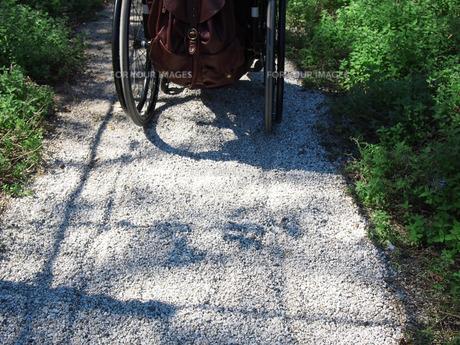 車いすで砂利道を走るの写真素材 [FYI00133227]