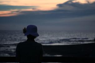 花飾りの帽子をかぶった女性と海の写真素材 [FYI00133642]