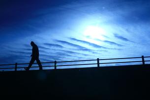 不思議な雲と歩く人の写真素材 [FYI00133645]