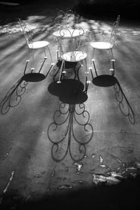 洋風の丸椅子とテーブルから伸びる影の写真素材 [FYI00133650]