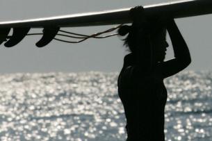 サーフボードを頭に抱える女性の素材 [FYI00133652]