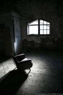 古い洋館の窓から差し込む光に照らされるソファの写真素材 [FYI00133672]