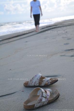 砂浜に置かれたサンダルと波打ち際を歩く女性の素材 [FYI00133678]