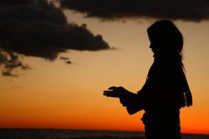 夕暮れに浮かぶ象徴的な女性のシルエットの写真素材 [FYI00133686]