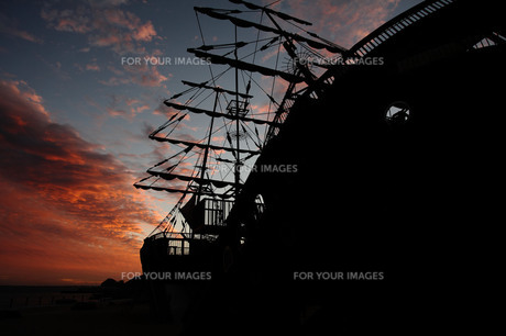 夕焼けに浮かぶ帆船のシルエットの写真素材 [FYI00133687]