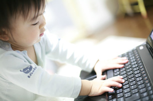 パソコンのキーボードをさわる子供の写真素材 [FYI00133749]
