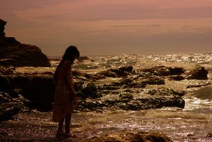 夕暮れの海岸に佇む少女の写真素材 [FYI00134470]
