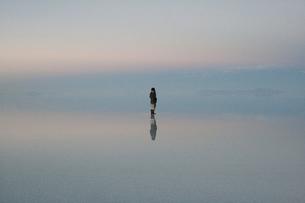 ウユニ塩湖、朝焼やけの中佇む人影の写真素材 [FYI00136266]