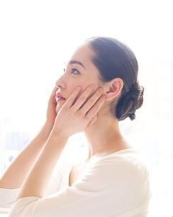 頬をなでる女性の写真素材 [FYI00143137]