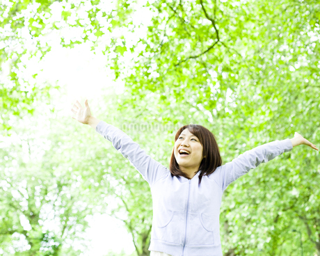 公園で手を広げる若い女性の写真素材 [FYI00143143]