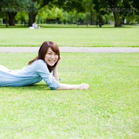 芝生に寝転んで笑顔の若い女性の素材 [FYI00143145]
