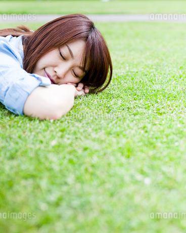 芝生に寝転んで寝ている若い女性の写真素材 [FYI00143148]