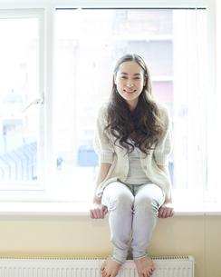 笑顔で窓辺に座る女性の写真素材 [FYI00143160]