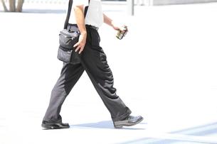 缶コーヒーを持って歩くビジネスマンの写真素材 [FYI00143527]