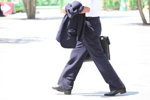 上着を手に持って歩くビジネスマンの写真素材 [FYI00143530]