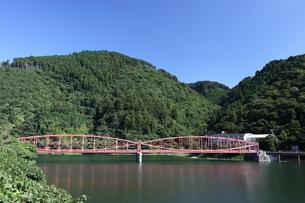 湖にかかる鉄橋と周囲の山と青空の写真素材 [FYI00143605]